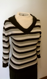 Grey, white, black striped v-neck sweater over black v-neck dress.