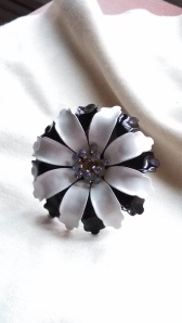 Black and white brooch, with blue rhinestones.
